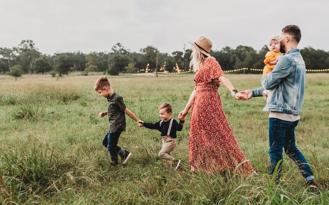 family of 4 walking through field