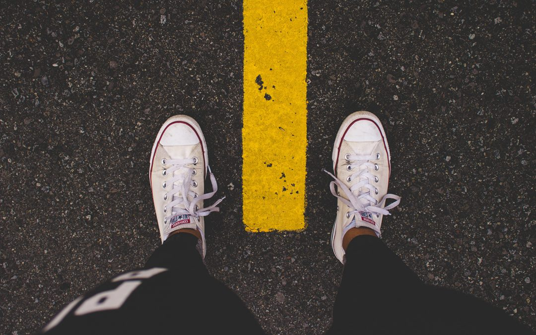 image of feet standing on a road with yellow line